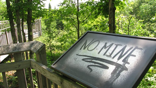An informational sign at a Penokee Range overlook near Mellen carries a spray-painted anti-mine message.