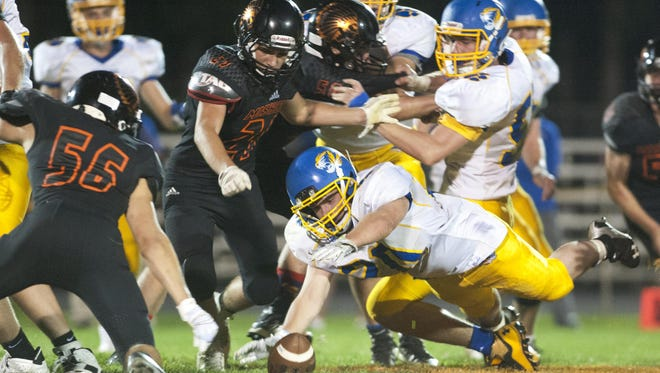Howards Grove running back Jacob Fritz (20) recovers the ball from a missed center quarterback exchange during the first half of the game against Mishicot Indians on Friday, Sept. 25 in Mishicot. The Tigers defeated the Indians 15-12.