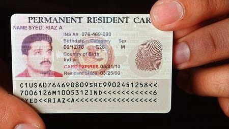Riaz Syed displays his green card, which lets him work in the United States permanently.