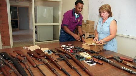 Anton Ragsdale, correction officer, left, and then-Council member Mary Rose Wilcox, look over an assortment of shotguns, rifles and handguns that were turned in by valley residents  during a 1999 gun buy-back program in Phoenix