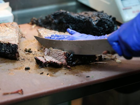 A cook slices brisket for a plate.