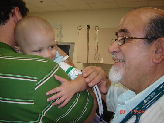Cross Kubik is held by his father Brian in a visit with an anesthesiologist at St. Jude Children's Research Hospital in Memphis in 2005.