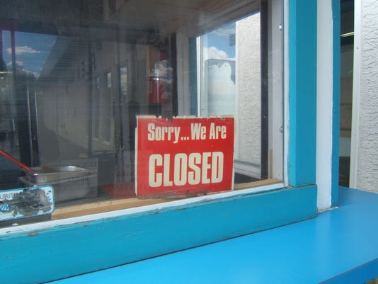 A red closed sign in the window of a blue building