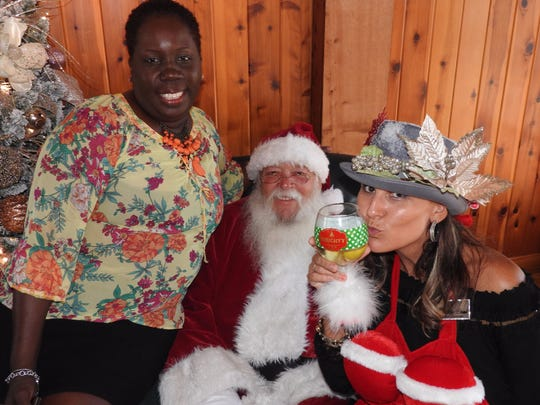 """From left, Carebag founder and CEO Rozanne """"Roxy"""" Brown, Santa Claus, and Deni Horna celebrate Christmas in July."""