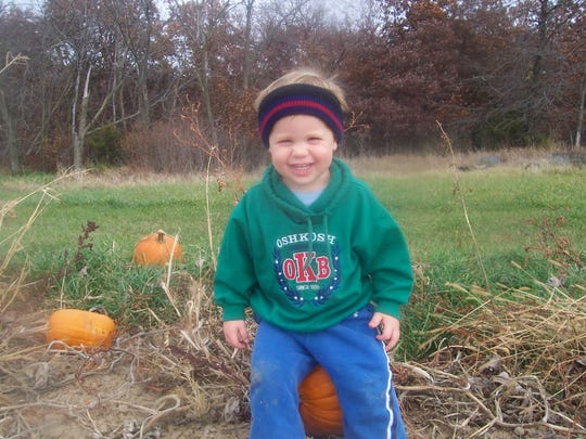 A tiny tot has takes a breather and uses a pumpkin