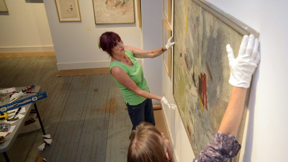 Sara LeDonne, left, and Black Mountain College Museum Program Director Alice Sebrell hand paintings for a new exhibit Saturday.