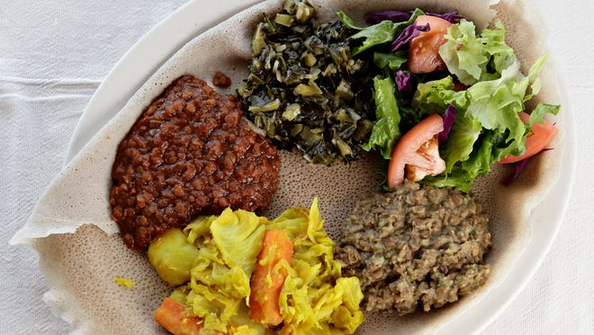A vegetable combination plate of Gomen, top, green salad, right, Misr Wat, lower right,Tikil Gomen, bottom, and Fosolia, left. All are Ethiopian specialties from Cafe Lalibela in Tempe.