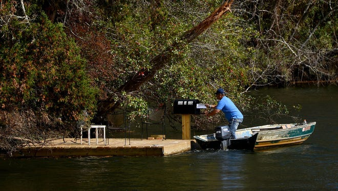 U.S. Postal Service carrier Mark Lipscomb pulls up to to a dock and drops off mail from his 15-foot aluminum boat Dec. 3 while delivering mail around Magnolia Springs, Ala.