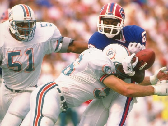 Miami Dolphins linebacker John Offerdahl breaks up