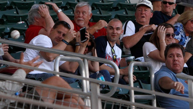 Baseball fans duck while trying to avoid getting hit with a foul ball Monday during a Red Sox vs  Northeastern University exhibition game at JetBlue Park in Fort Myers.