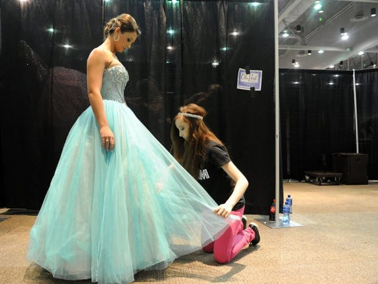 Kierstyn Farrar fluffs a dress backstage for model, Johnna Snider, 15, at the 6th annual Wedding and Prom Showcase at The Centre in 2014. Snider was modeling for The Graceful Lady. More than 100 vendors were on hand offering everything from cakes to dresses to photography.