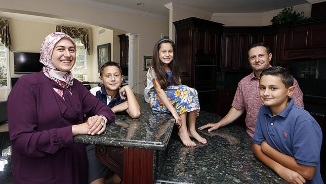 Ranya Shbeib poses with her family, from left, Kareem Obeid, 11; Lana Obeid, 7; husband Anas Obeid, and Adel Obeid, 12, in their Bloomfield Hills home. Last year, a Somali teen in need of foster care in the United States stayed with the family.
