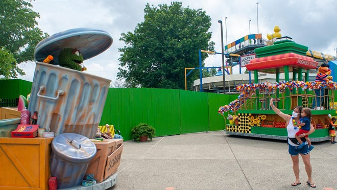 Lily Castilla of Queens, New York, holds Asher Duverge as they wave to Oscar the Grouch from a distance during the opening day Friday of Sesame Place in Middletown. Guests must practice social distancing at all times, including from characters.