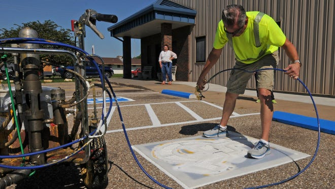 Jason Trojcak, with Clean Line Parking Lot Striping, paints a handicap sign at the Salina Emergency Aid Food Bank as Karen Couch, executive director of the Salina Emergency Aid Food Bank, watches on Saturday. Trojcak volunteered his time and supplies to paint the parking lot lines at the food bank.