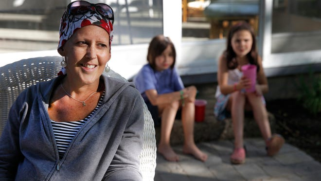 From left, Anne Mowrer, enjoys her new patio with Annie Adamson and her daughter, Ellie Mowrer. Anne is undergoing treatment for metastatic breast cancer. So when she was out of town one weekend in May, friends and neighbors came by and built the patio.