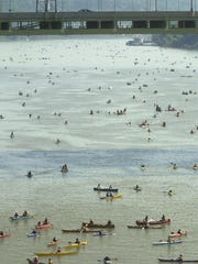 Participants paddle their canoes and kayaks during the 2003 Ohio River Way Paddlefest 8.2 mile leisurely float trip on the Ohio River , near downtown Cincinnati.