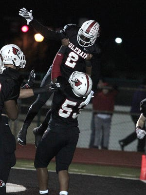 George Williams holds up his quarterback Deshaunte Jones after Jones takes it in for a Colerain touchdown.  Elder and Colerain meet in the much anticipated Regional Final at Mason High School Saturday Night, November 21st, 2015.