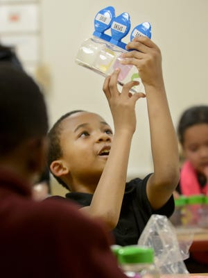 Andrew Jackson Elementary School  second-grader Marquez Nesby counts his pennies in class, Tuesday afternoon. The money jar was a gift from Union University Economics Professor Colene Trent and her economics class.