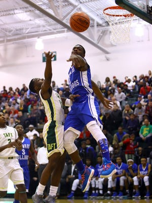 Woodward forward Terry Durham rejects the shot of Taft guard Derrick Heard in the OHSAA District Semi-Final game between the Taft Senators and the Woodward Bulldogs at Mason High School in Mason, Ohio.