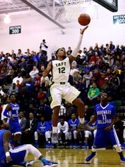Taft guard DaShawn Lawrence drives and scores in the OHSAA District Semi-Final game between the Taft Senators and the Woodward Bulldogs at Mason High School in Mason, Ohio.
