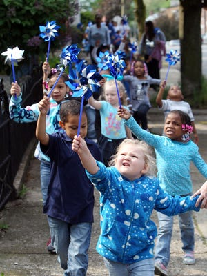 Jayden Green and other children from Covington's Northern Kentucky Head Start program hold their pinwheels high as they march down Philadelphia Street in a Child Abuse Awareness Walk in 2012.