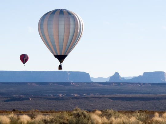 A hot air balloon participating in the 13th annual Page Lake Powell Hot Air Balloon Regatta floats in the skies above Page Sunday, Nov. 8, 2015. A weekend filled with fantastic ballooning weather saw 60 hot air balloons filling the skies over Lake Powell on Friday, Saturday and Sunday mornings. In additions, about 20 of the balloons were lined up along Lake Powell Boulevard Saturday night for a balloon glow and street festival.