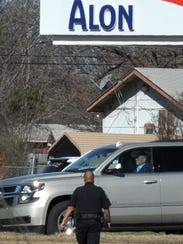 A Wichita Falls police officer searches the area for
