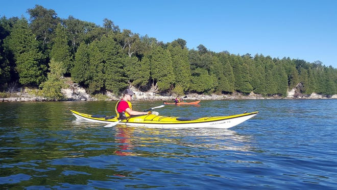 Evan Gorelick (front) and Katie O'Connell paddle along the southern shore of Rock Island State Park north of Door County.
