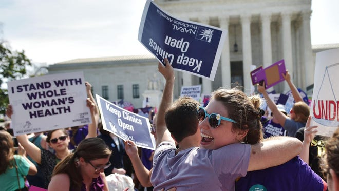 Abortion rights activists embrace Monday after the U.S. Supreme Court struck down a Texas law placing restrictions on abortion clinics.