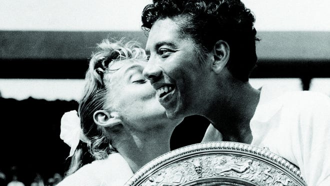 Althea Gibson is kissed by her finals opponent Darlene Hard at Wimbledon in 1957.