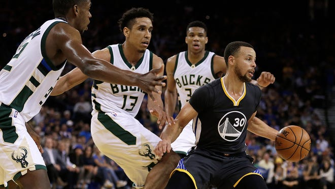 Golden State's Stephen Curry is chased by Bucks players  (from left) Khris Middleton, Malcolm Brogdon and Giannis Antetokounmpo during their game Saturday night.