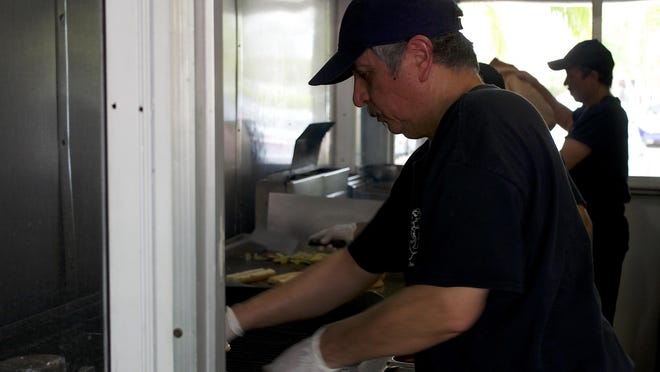 Employees work in the kitchen at Dune Dog Cafe in Jupiter last year.