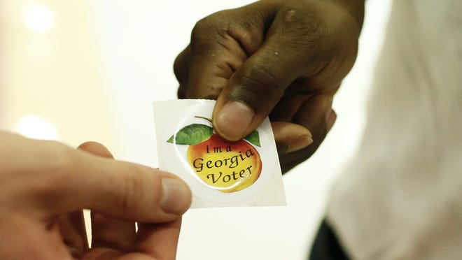 """A voters picks up an """"I'm a Georgia Voter,"""" sticker after voting on Tuesday, Nov. 3, 2020."""