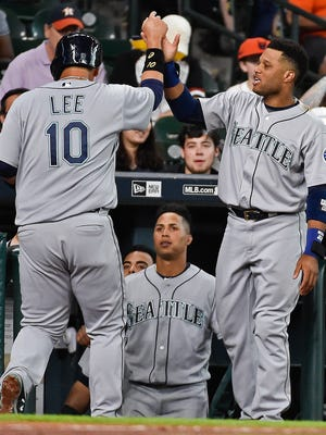 Seattle Mariners' Dae-Ho Lee (10) celebrates scoring a run on a fielder's choice with Robinson Cano in the second inning of a baseball game against the Houston Astros, Tuesday, July 5, 2016, in Houston.