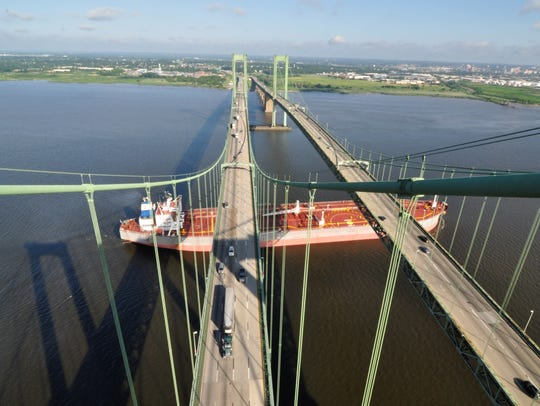 A cargo ship passes under the Delaware Memorial Bridge twin spans.
