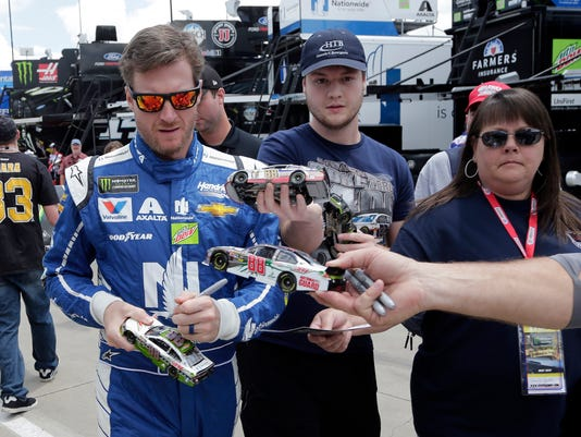 Dale Earnhardt Jr. signs autographs before practice for Sunday's NASCAR Cup series auto race at Charlotte Motor Speedway in Concord, N.C., Thursday, May 25, 2017. (AP Photo/Chuck Burton)