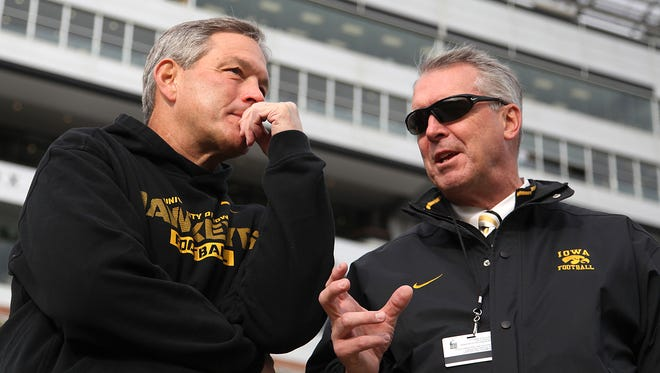 Iowa head football coach Kirk Ferentz, left, and athletic director Gary Barta talk before a game in 2013. Barta and the Iowa athletic department have been revamping fans' gameday experience at Kinnick Stadium the past week as the deadline for season ticket renewals approaches.