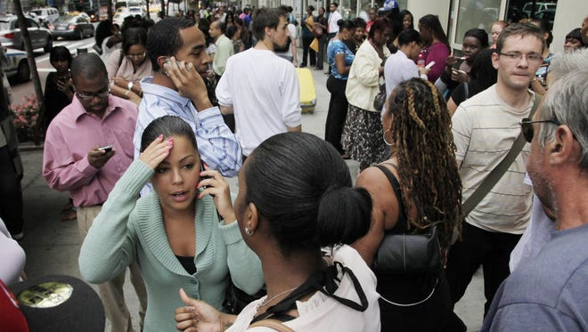 Office workers gather on a sidewalk after their building was evacuated following a 2011 earthquake in New York.