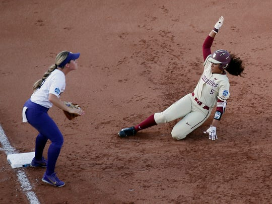 Florida State catcher Elizabeth Mason (5) slides safely into third base as Washington's Taylor Van Zee, left, waits for the throw during the second inning of the second game of the best-of-three championship series in the NCAA softball Women's College World Series in Oklahoma City, Tuesday, June 5, 2018. (AP Photo/Sue Ogrocki)