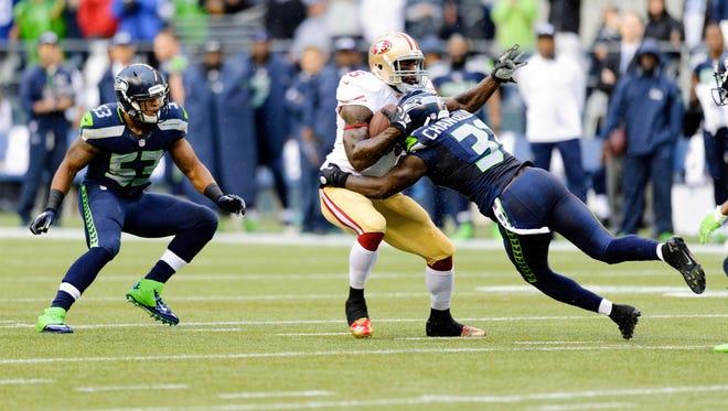 Seattle Seahawks strong safety Kam Chancellor (31) tackles San Francisco 49ers tight end Vernon Davis (85).
