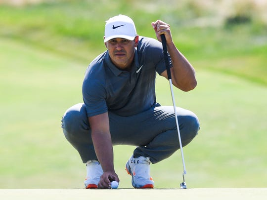 Brooks Koepka lines up a putt on the fifth green during
