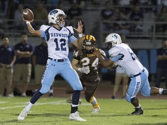 Redwood quarterback Frankie Ayon fires a pass against Golden West in September at Groppetti Automotive Visalia Community Stadium.