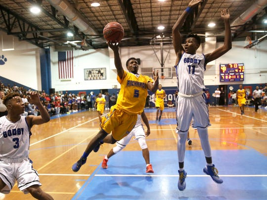 Rickards' Vincent McCray tries to lay the ball up past the defense of Godby's Corbin Merritt during their game at Godby High School on Friday, Jan. 6, 2017.