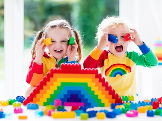 Little kids playing with colorful blocks