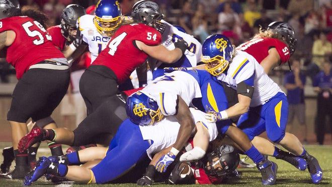 South Dakota State tacklers pile on Southern Utah fullback Toa Afatasion during a 2014 football game.