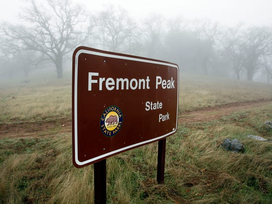 A sign at the entrance of Fremont Peak stands alone in the fog and drizzle