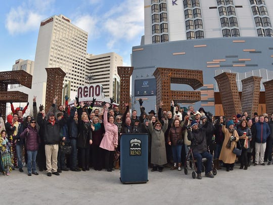 """A group photo is taken after the dedication ceremony for the BELIEVE art piece in downtown Reno on Dec. 31. RGJ Citizen of the Year Jeff Bryant read a proclamation declaring Thursday as """"Believe in Reno Day."""""""