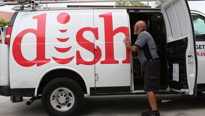 Alberto Rodriguez, a Dish Network technician works around one of the company trucks on June 4, 2015 in Miami, Florida.