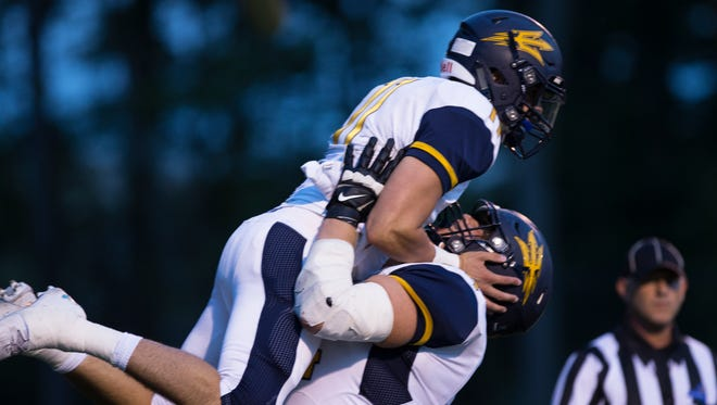 Victor's Jamie Trimboli is lifted up in celebration after he makes the first touchdown of the game against Victor at Webster Thomas High School on Friday, September 11, 2015.