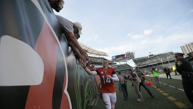 Cincinnati Bengals quarterback Andy Dalton (14) high-fives fans as he heads for the locker room after the fourth quarter of the NFL Week 4 game between the Cincinnati Bengals and the Kansas City Chiefs at Paul Brown Stadium in Cincinnati on Sunday, Oct. 4, 2015. The Bengals advanced to 4-0 with a 36-21 win at home.